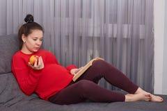 Горизонтальная съемка сконцентрированной женщины с темными волосами, имеет tummy, предвидит для ребенка, сидит босоногое на софе, стоковые фото
