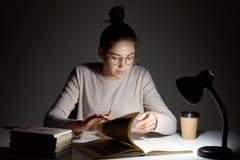 Горизонтальная съемка сфокусированного женского ученого кантует страницы в книге, ищет необходимую информацию, выпивает горячий к стоковые фото
