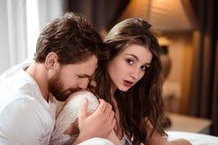 Горизонтальная съемка atrractive мужчины целует его женского любовника в плече, срочной влюбленности и страсть, тратит свободное  стоковые изображения rf