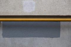 Горизонтальная труба газа покрашенная с желтой краской рядом с стеной здания Текстура бетона Прямоугольник серой краски стоковая фотография rf