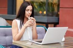Горизонтальная concentared съемка хорошего смотрящ напиток молодых женских модельных глоточков вкусный, на современном портативно стоковая фотография rf