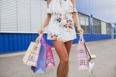 Горизонтальное фото конца-вверх сногсшибательных ног на покупках, стоящ с красочными хозяйственными сумками, ходя по магазинам ко Стоковые Изображения RF