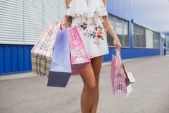 Горизонтальное фото конца-вверх сногсшибательных ног на покупках, стоящ с красочными хозяйственными сумками, ходя по магазинам ко Стоковая Фотография RF