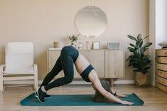 Горизонтальный взгляд женщины делая йогу дома Стоковые Изображения