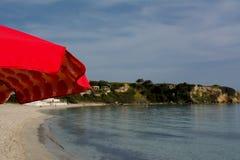 Горизонтальный взгляд красного зонтика пляжа на береговой линии Backgr нерезкости Стоковая Фотография
