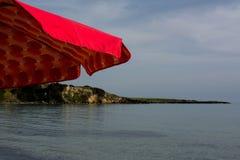 Горизонтальный взгляд красного зонтика пляжа на береговой линии Backgr нерезкости Стоковое Фото