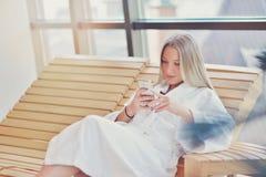 Горизонтальный взгляд чая женщины выпивая в курорте Стоковая Фотография
