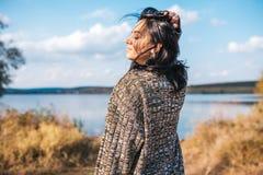 Горизонтальный вид сзади красивой женщины с дуя волосами ослабляя и наслаждаясь природу рядом с озером outdoors кавказско стоковое фото