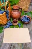 Горизонтальный лист бумаги кладет около корзины, шара с виноградинами, опарника и чашки с вином на деревенскую древесину Стоковые Фотографии RF