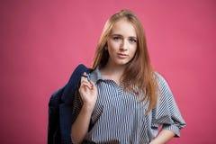 Горизонтальный портрет красивой красной с волосами девушки студента на розовой предпосылке Молодая женщина носит striped блузку и стоковые фотографии rf