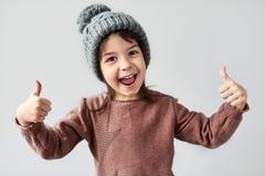 Горизонтальный портрет крупного плана счастливой усмехаясь маленькой девочки в шляпе зимы теплой серой, нося свитера и показывать стоковое изображение