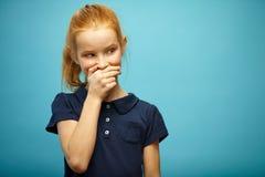 Горизонтальный портрет лукавой freckled девушки с красными волосами покрывает ее рот и смотрит прочь на предпосылке изолированной Стоковое Фото