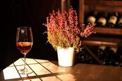 Горизонтальный романтичный состав бокала вина и цветочного горшка помещенных на таблице в winehouse Стоковое Фото