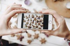 Горизонтальный телефон в руках женщины над таблицей с печеньями стоковые изображения