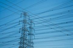 Горизонтальная съемка высоковольтных башен silhouetted против сини Стоковые Фотографии RF