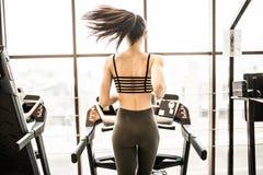 Горизонтальная съемка женщины jogging на третбане на оздоровительном клубе Женская разработка на спортзале бежать на третбане Стоковое Изображение