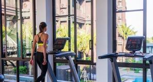 Горизонтальная съемка женщины jogging на третбане на спортивном клубе здоровья на роскошном курорте Женская разработка на ходе сп Стоковая Фотография RF