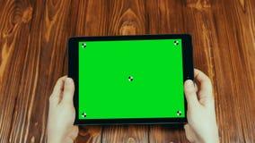 Горизонтальная таблетка с зеленым экраном в руках сток-видео