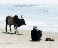Горизонтальные яркие человек и корова на Индийском океане приставают к берегу Стоковое Изображение