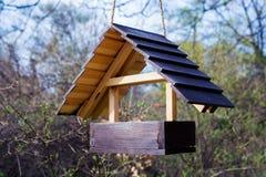 Горизонтальный взгляд новой деревянной смертной казни через повешение birdhouse на дереве Стоковое фото RF
