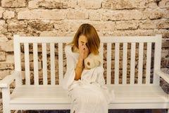 Горизонтальный взгляд плача девочка-подростка обернутого в шотландке пока сидящ на белом стенде Стоковое Изображение
