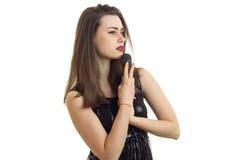 Горизонтальный портрет красивой девушки с микрофоном в ее руке и черном платье Стоковые Фото