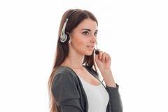 Горизонтальный портрет молодой симпатичной девушки работника офиса звонка при наушники и микрофон изолированные на белой предпосы Стоковые Изображения