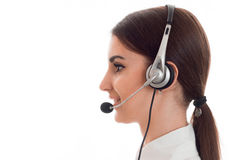Горизонтальный портрет профиля молодой жизнерадостной девушки работника офиса звонка при наушники и микрофон изолированные на бел Стоковое Фото