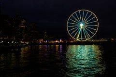 Горизонт города Сиэтл Вашингтона & колесо Ferris на причале поздно вечером стоковое фото