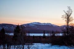 Горная цепь и замороженное озеро на заходе солнца в зиме Стоковые Изображения RF