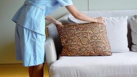 Горничная кладет подушку на софу сток-видео
