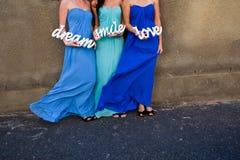 Горничные невесты женщины в красочных голубых платьях задерживают знак Улыбка, любовь и мечта стоковая фотография rf