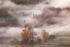 Горное село в облаках тумана и дым в mornin осени Стоковые Изображения
