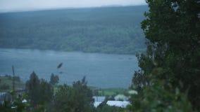 Горное село на банках реки зажим Взгляд реки около деревни в пасмурных погоде и сильных ветерах сток-видео