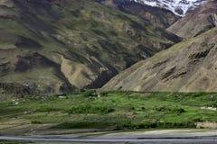 Горное село на речном береге, зеленых полях, деревьях, крестьянских домах, на заднем плане ровных наклонах коричневых гор Стоковое Изображение RF