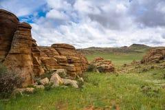 Горные породы и зеленое поле Стоковое Фото