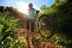 Горный велосипед нося велосипедиста женщины взбираясь на следе леса лета Стоковые Фотографии RF