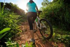 Горный велосипед нося велосипедиста женщины взбираясь на следе леса лета Стоковые Изображения RF