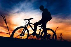 Горный велосипед катания велосипедиста спортсмена на заходе солнца Стоковые Изображения RF