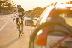 Горный велосипед катания человека велосипедиста на заходе солнца на дороге горы Стоковые Изображения RF