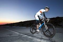 Горный велосипед катания человека велосипедиста на заходе солнца на дороге горы Стоковое Фото