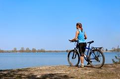 Горный велосипед молодой женщины стоит на банке  Стоковая Фотография RF