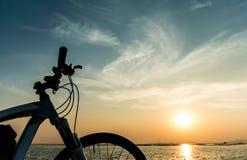 Горный велосипед паркуя на море и предпосылка неба захода солнца Стоковые Фотографии RF