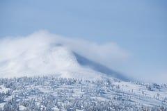 Горный пик в снеге и облаках стоковое изображение