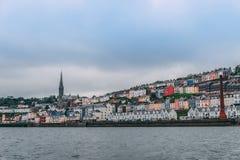 Городок Cobh, которое сидит на острове в city's пробочки затаивает, как увидено от моря стоковое изображение rf