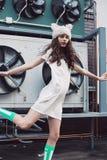 Городская девушка в белом платье и меховой шапке представляя в городе Стоковые Фото