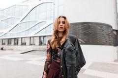 Городская молодая женщина в ультрамодной сделанной по образцу блузке с винтажной кожаной курткой в брюках с красивым макияжем сто стоковое фото
