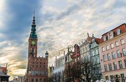 Городская ратуша со шпилем, башней с часами, фасадом красивых типичных красочных зданий домов на targ Dlugi улицы длинного рынка  стоковые фото