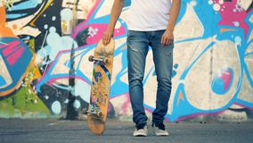 Городская стена граффити с молодым человеком поднимая его скейтборд фокусом ноги видеоматериал