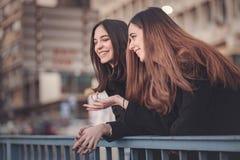 Городские девушки наслаждаясь днем вне в городе Стоковая Фотография